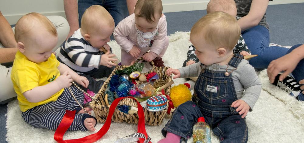 Babies play with treasure basket